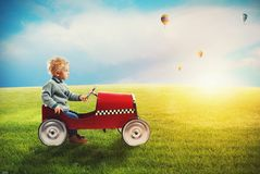 Child with car plays in a green field. During sunrise Royalty Free Stock Photo