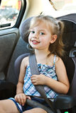 Child in car seat. Little girl in a car seat smiling at the camera Royalty Free Stock Images