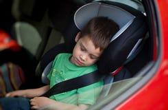 Child in car seat wearing belt. Child sleeping in car seat, wearing safety belt Royalty Free Stock Photos