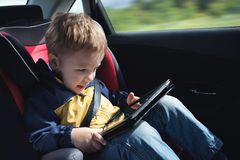 Child in the car with tablet PC Royalty Free Stock Photo