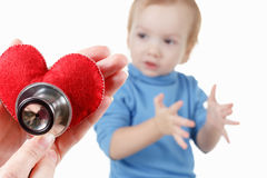 Child and cardiologist, heart symbol in hand, stethoscope. Stock Photo