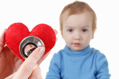 Child and cardiologist, heart symbol in hand, stethoscope. Stock Photography