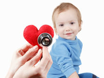 Child and cardiologist, heart symbol in hand, stethoscope. Concept of health and care. Baby and cardiologist, heart symbol in hand and stethoscope royalty free stock images