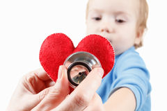 Child and cardiologist, heart symbol in hand, stethoscope. Stock Photos