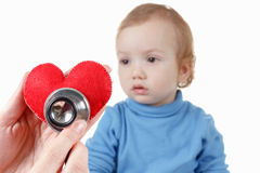 Child and cardiologist, heart symbol in hand, stethoscope. Royalty Free Stock Photos
