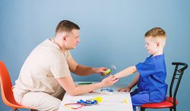 Child care. Careful pediatrician check health of kid. Medical examination. Medical service. Man doctor sit table medical royalty free stock photos