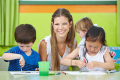 Child care worker with children. Happy child care worker with children drawing in a kindergarten Royalty Free Stock Photography
