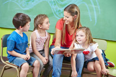 Child care worker and children. Reading a picture book together in a kindergarten Stock Photos