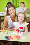 Child care worker with girl. Happy child care worker helping girl painting in a kindergarten Royalty Free Stock Photography