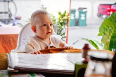 The child carefully looks ahead. Infant girl is sitting on a baby`s high chair in a street cafe.  Children  reading chooses and. Infant girl is sitting on a baby royalty free stock photography