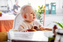 The child carefully looks ahead. Infant girl is sitting on a baby`s high chair in a street cafe.  Children  reading chooses and. The child carefully looks ahead stock images