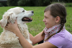Child caressing dog on a meadow Stock Images