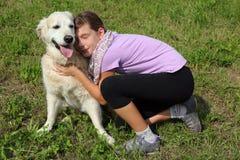 Child caressing her pet dog Royalty Free Stock Image