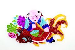 Child and Carp. An immortal child in traditional Chinese clothes holding a big carp, with a lotus seedpod in his hand, and peonies behind Royalty Free Stock Image