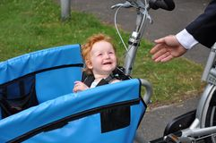 Child in carrier bike says bye to daddy. Child in carrier bicycle says goodbye to daddy Royalty Free Stock Image
