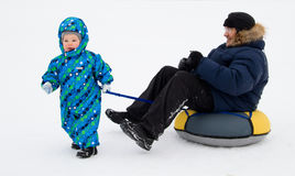 A child carries on dad tubing (inflatable sled). Winter. Russia Royalty Free Stock Photos