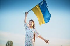 Child carries fluttering blue and yellow flag of Ukraine. In lupine field. Ukraine`s Independence Day. Flag Day royalty free stock image