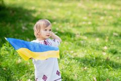 Child carries fluttering blue and yellow flag of Ukraine in field. Ukraine`s Independence Day. Flag Day. Constitution day. Girl i. N traditional embroidery with royalty free stock photography
