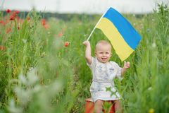 Child carries fluttering blue and yellow flag of Ukraine in field. Ukraine`s Independence Day. Flag Day. Constitution day. Girl i. N traditional embroidery with royalty free stock image