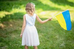 Child carries fluttering blue and yellow flag of Ukraine in field. Ukraine`s Independence Day. Flag Day. Constitution day. Girl i. N traditional embroidery with stock photos