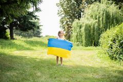Child carries fluttering blue and yellow flag of Ukraine in field. Ukraine`s Independence Day. Flag Day. Constitution day. Girl i. N traditional embroidery with royalty free stock photos