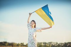 Child carries fluttering blue and yellow flag of Ukraine. In lupine field. Ukraine`s Independence Day. Flag Day stock photography
