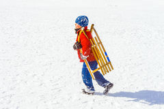 Child carries his sledge Royalty Free Stock Photography