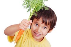 Child with a carrot in hand. A little cute child holding a fresh carrot in hand Stock Photography