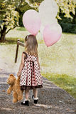 Child Carrying Balloons And Dragging Her Teddy Royalty Free Stock Photography