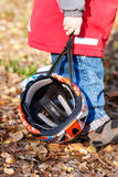 Child carrying his cycling helmet. Outdoor cycling in park with kids. A weekend in November stock photography