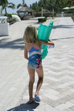 Child carrying inflatable toy. Child in swimming costume carrying inflatable beach toy, seen from behind Royalty Free Stock Photo
