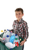 Child carrying recycling. A child carrying a plastic container full with empty recyclable household material stock images