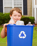 Child carrying recycling bin. Recycling concept with young child carrying recycling bin royalty free stock photography