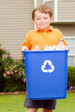 Child carrying recycling bin. Recycling concept with young child carrying recycling bin Royalty Free Stock Images