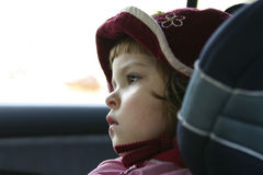 Child in a carseat. Little girl wearing hat in a safety car seat Stock Photos