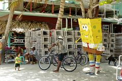 Child by a cartoon statue. Child and man on a bicycle by a Sponge Bob cartoon statue in front of wooden lobster traps on the beach on Caye Caulker, Belize Royalty Free Stock Photo