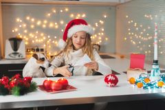 Child carves a snowflake for christmas. Girl is making decoration for the new year Stock Image