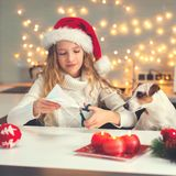Child carves a snowflake for christmas. Girl is making decoration for the new year Royalty Free Stock Image