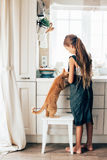 Child with cat at the kitchen. Kid girl feeding ginger cat at the kitchen Stock Photo
