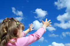 The child catches a cloud two hands. The girl catches a cloud two hands against the sky Stock Photography
