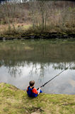 A child catches a fish in the river Royalty Free Stock Photography