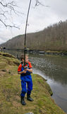 A child catches a fish in the river Stock Photography