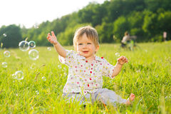 Child catches a soap bubbles. Royalty Free Stock Image
