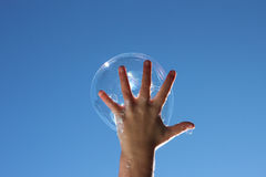 Child catching bubble. Happy child catches a bubble in one hand on a sunny day against a deep blue sky royalty free stock image