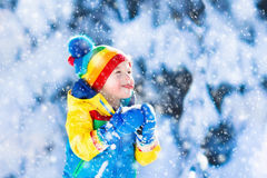 Child catching snow in winter park Stock Photography