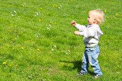 Child catching soap bubbles Royalty Free Stock Photos