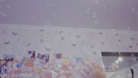 Child catching soap bubbles stock video