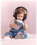 Child with CD discs in ear-phones Royalty Free Stock Photo