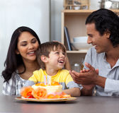 Child celebrating his birthday with his parents. Joyful child celebrating his birthday with his parents in the kitchen Royalty Free Stock Image