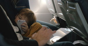 Child with cell and and man using pad in plane. Little boy bored with flight using smartphone lying on mothers lap and his father working with tablet computer stock video footage